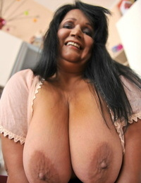 BBW brown-haired Bubi poses and demonstrates her big innate boobs in a kitchen